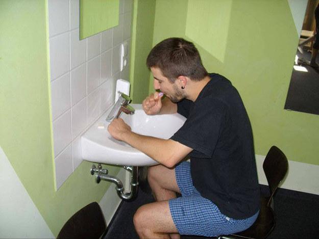 chico sentado frente a un lavamanos lavándose los dientes