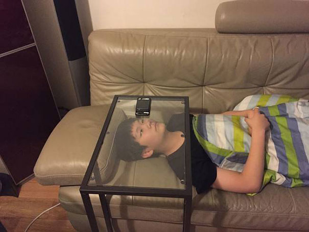 chico viendo su celular acostado en el sillón a través de una mesa de vidrio
