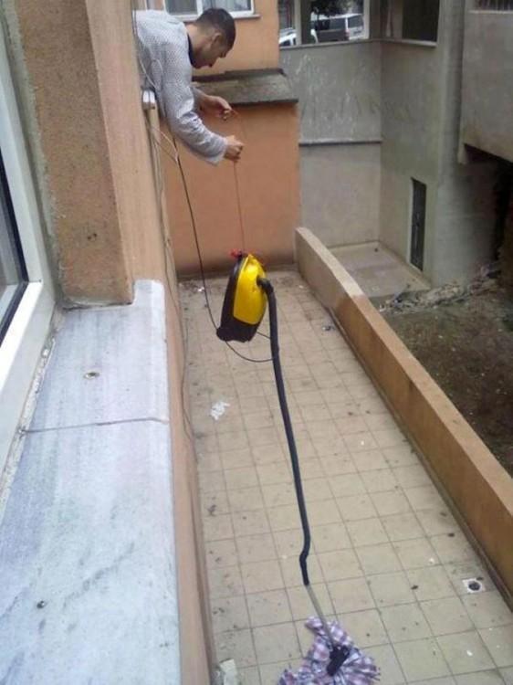 hombre levantando una camisa del piso con una aspiradora desde un segundo piso