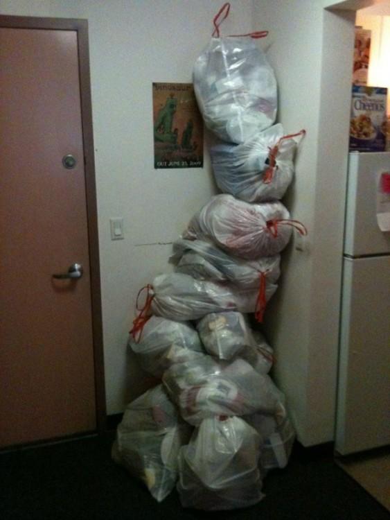 Bolsas de basura blanca amontonadas en la esquina de una casa