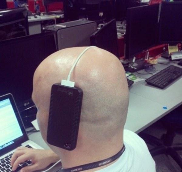 Hombre que tiene el celular sostenido con un cable blanco que le atraviesa la cabeza
