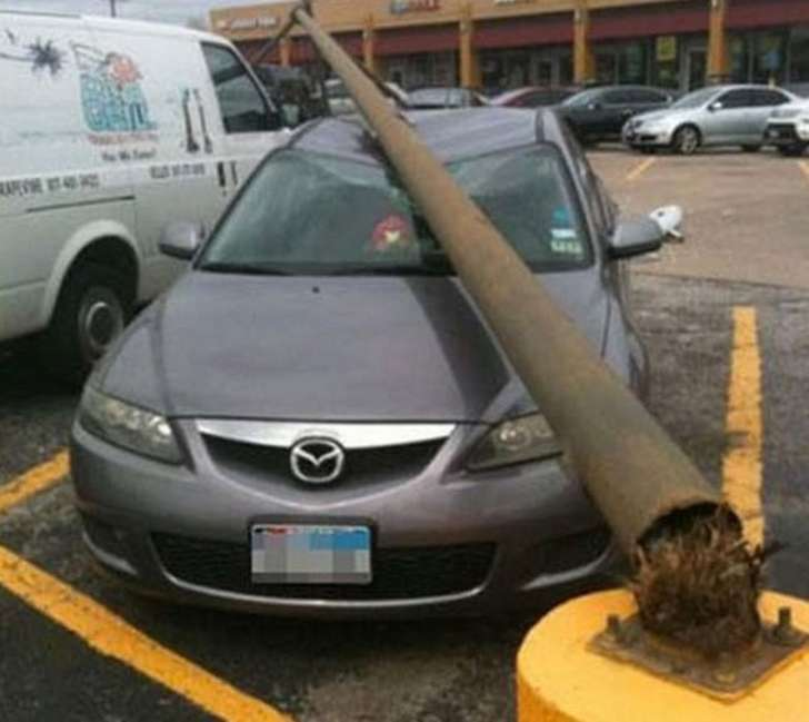 imagen que muestra un poste que cayó sobre un coche estacionado