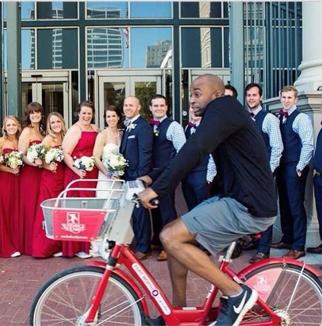 Chico en bicicleta atravesando en medio de una sesión de fotos de una boda