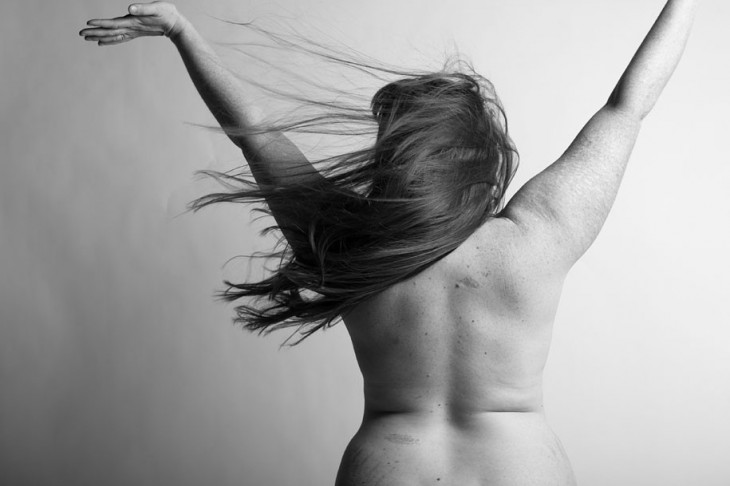 mujer desnuda de espaldas levantando sus manos hacia arriba