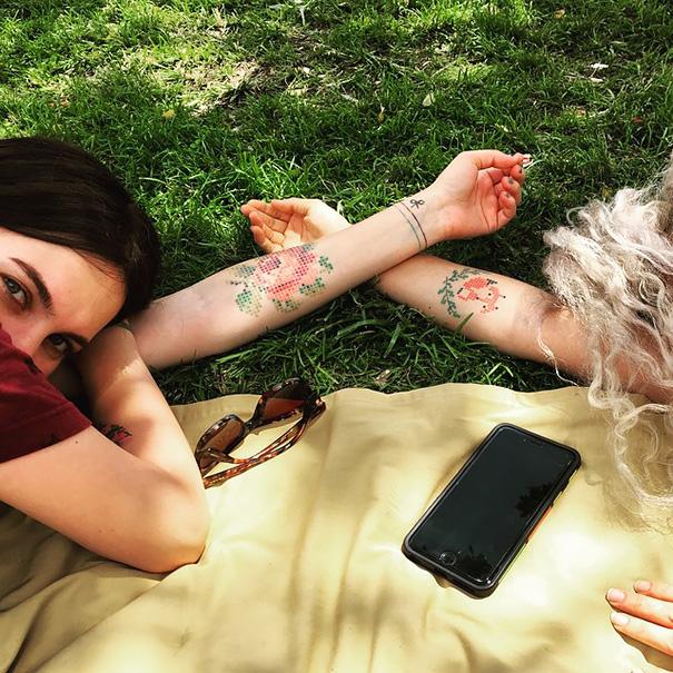 chicas acostadas mostrando sus tatuajes en punto de cruz