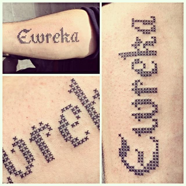 tatuaje de una frase en punto de cruz sobre el brazo de un hombre