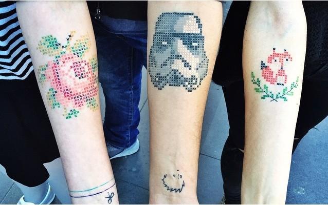 Tatuajes en forma de cruz con la figura de una rosa, Darth Vader y un zorro en los brazos de personas