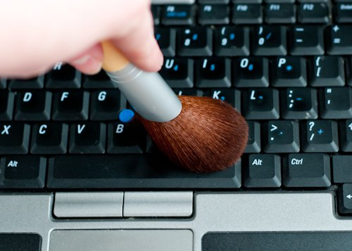 Mano de una persona limpiando el teclado de una computadora con una brocha