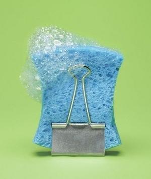 Esponja para lavar los trastes sostenida con un clip de mariposa