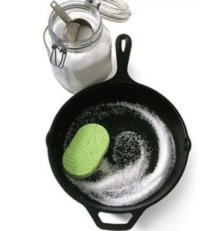 Sartén con una esponja y sal dentro de él junto a un frasco lleno de sal
