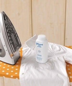 Plancha junto a una camisa de color blanco con un frasco de talco sobre ella