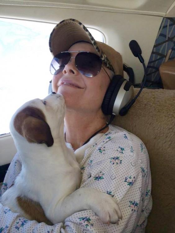 Voluntaria de la organización alas de rescate con un perro arriba de un avión
