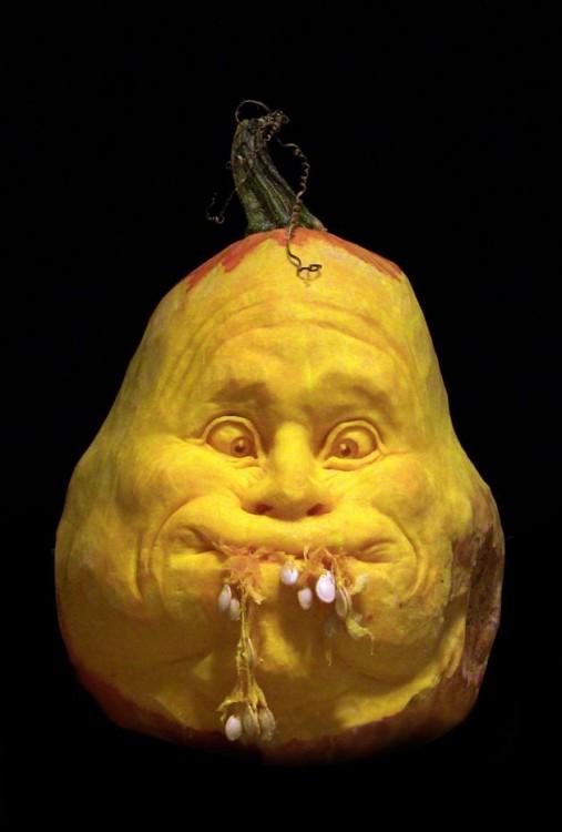 arte con calabazas en forma de una cara simulando que se le sale la comida de la boca