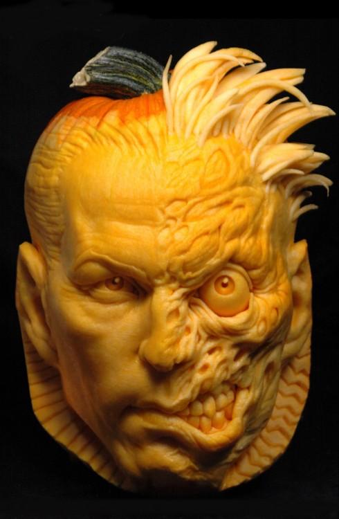 Arte con calabazas en forma de cara con la mitad de calavera y cabello