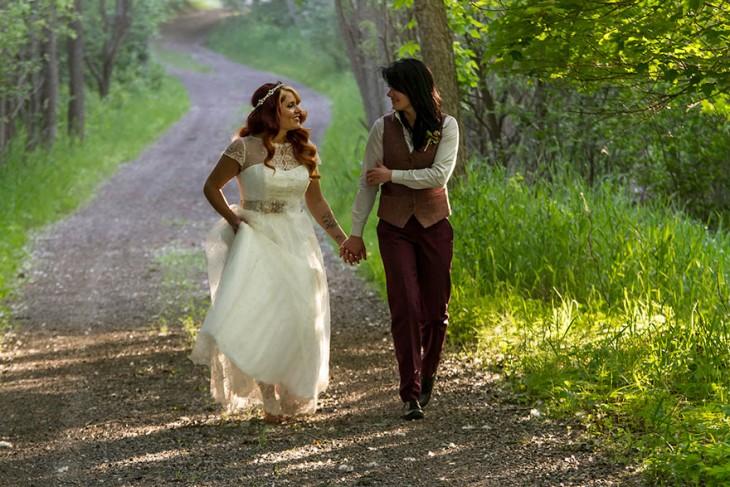 Lindsay And Leslie agarradas de la mano caminando por un camino rodeado de áreas verdes