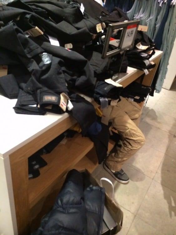 Niño acostado en un estante de pantalones en el centro comercial