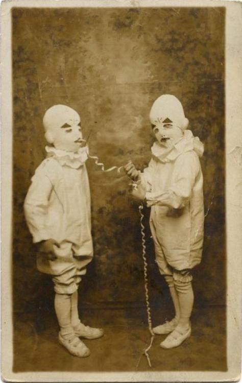 niño sacandole serpentidnas de la boca a su hermano que tambien esta disfrazado de arlequin