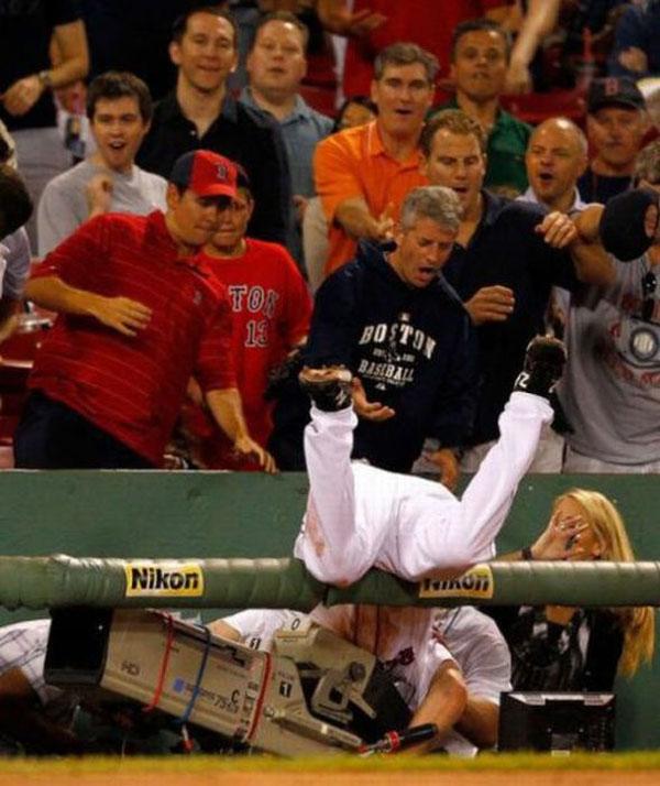 jugador de beisbol cae sobre la camara y el publico vip