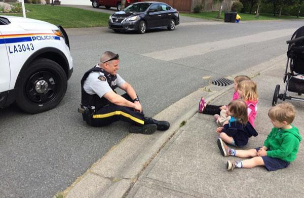 policia jugando con niñas en la calle tirado en la banqueta