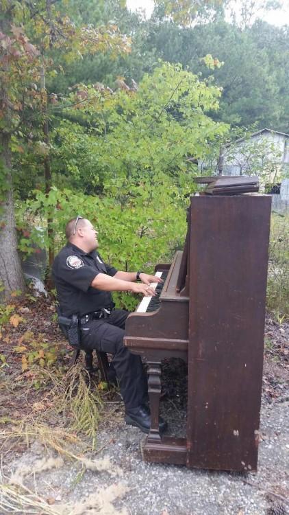 ´policia hace que toca el piano en un jardin abandonado