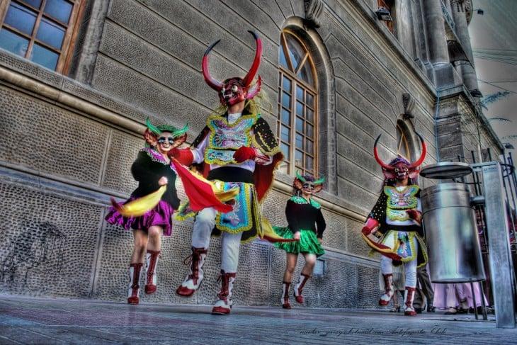 Personas bailando la diablada en una de las calles de Bolivia