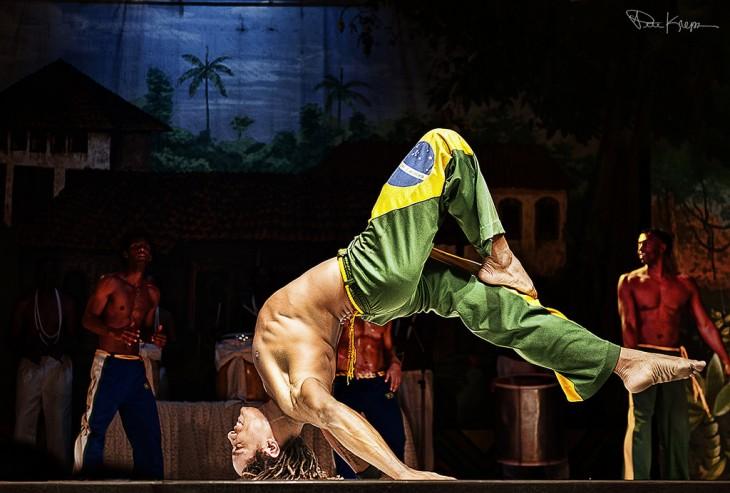 Hombre en el escenario de un teatro bailando capoeira