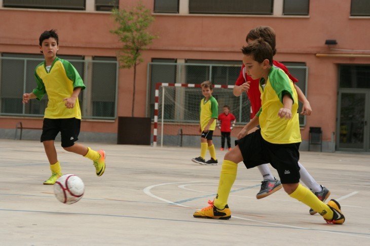 Niños en el patio de una escuela jugando fútbol