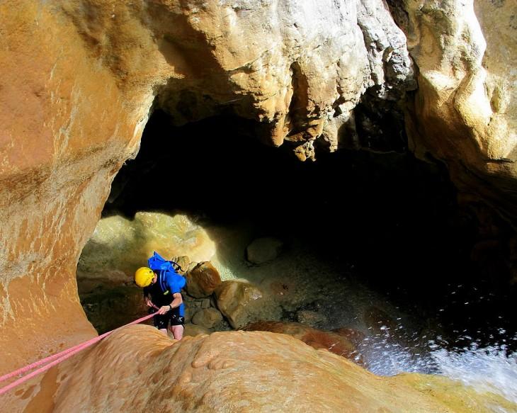 Chico haciendo Rápel en la cueva del barranco de Arandari, España