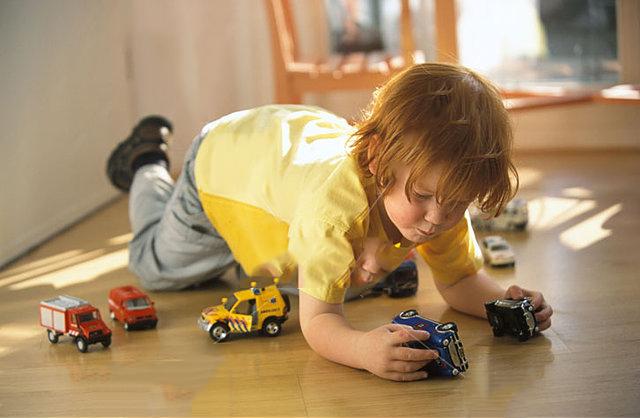 niño jugando a los carritos en el piso