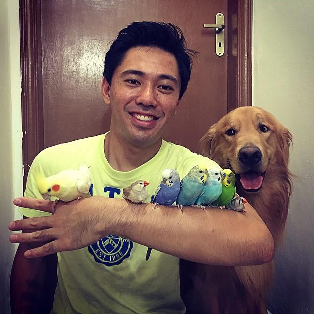 un hombre sosteniendo algunas aves en su brazo junto a un perro