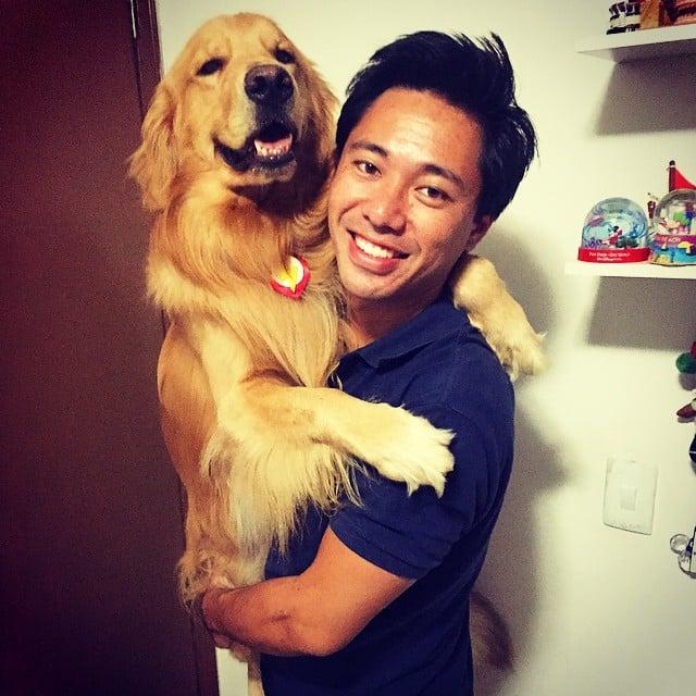 chico cargando a un enorme perro en su brazos