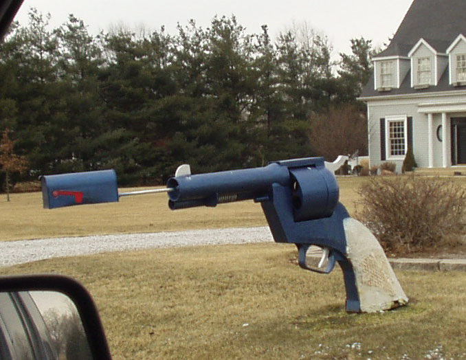 Pistola afuera de una casa de la cual sale el buzón de correo