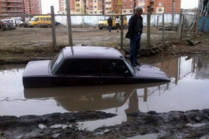 un carro hundido en agua en medio de la calle