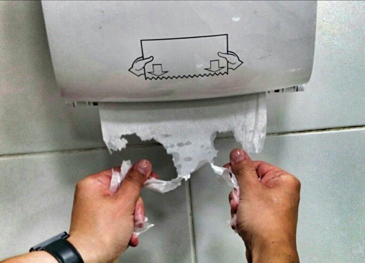 Manos que rompen el papel al intentar secar sus manos