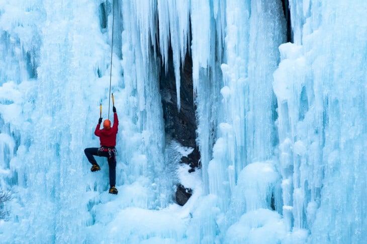Persona escalando sobre una montaña con nieve