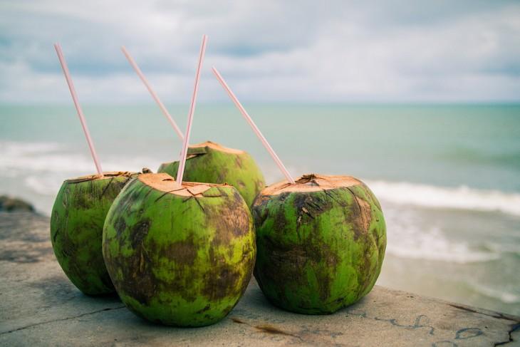 Cocos con popotes sobre una superficie frente a una playa