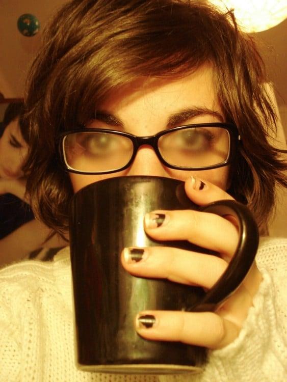 Chica tomando una bebida caliente y con sus lentes empañados