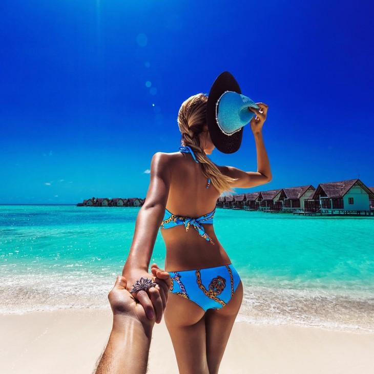 Chica con un bikini azul frente a una playa