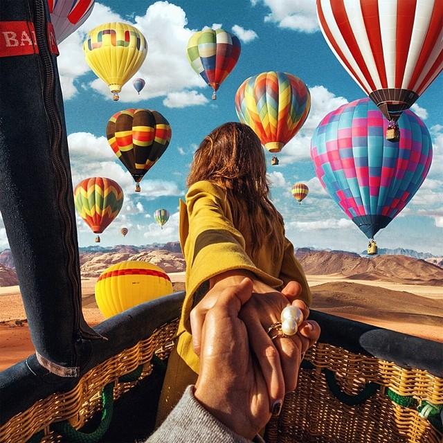 Una chica sobre un globo aerostático con una vista de otros globos y montañas