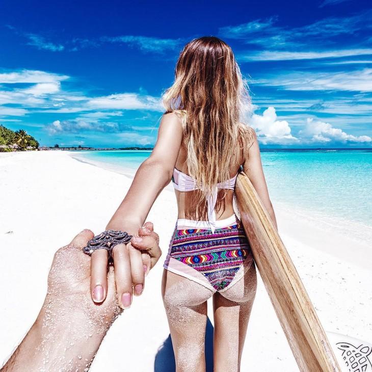chica en bikini cargando una tabla de surf caminando a la orilla de una playa