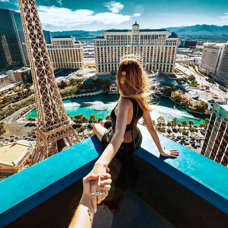 chica sentada en un balcón admirando el paisaje debajo de ella