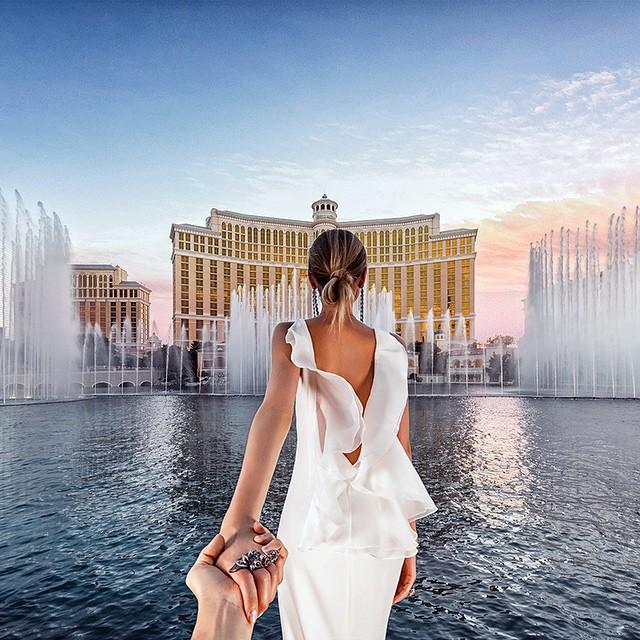 Mujer frente a un paisaje de un lago frente a edificios en Las Vegas