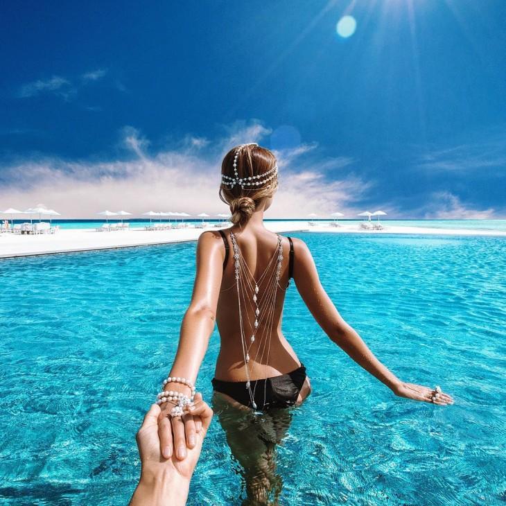 Mujer con un bikini negro dentro del agua en la playa