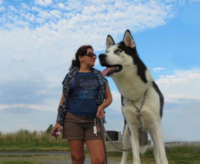 Mujer a un costado de un perro husky