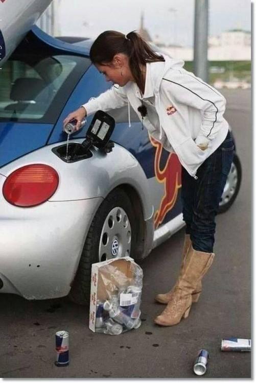 Mujer vertiendo un red bull en el tanque de gasolina de un coche