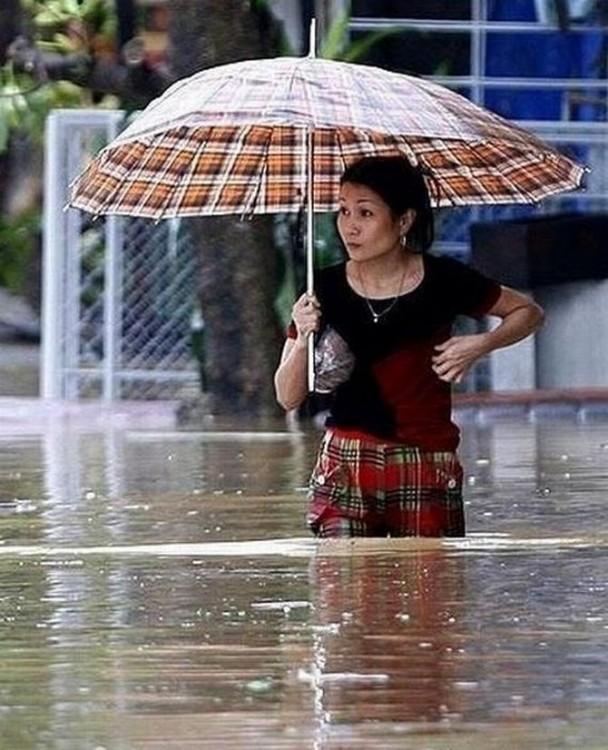 Mujer caminando sobre el agua con un paraguas