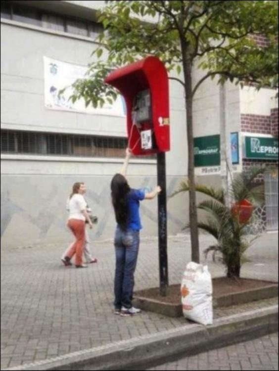 Chica intentando descolgar un teléfono demasiado alto