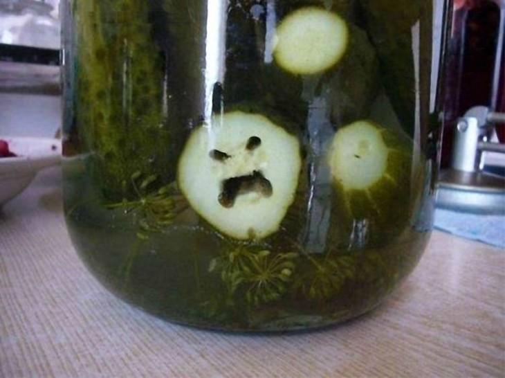 Rodaja de pepino con cara enojada dentro de un frasco con agua