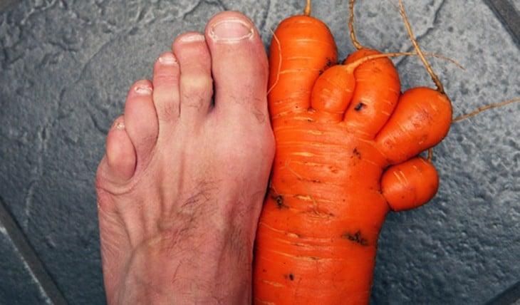 Zanahoria en forma de pie junto al pie de una persona