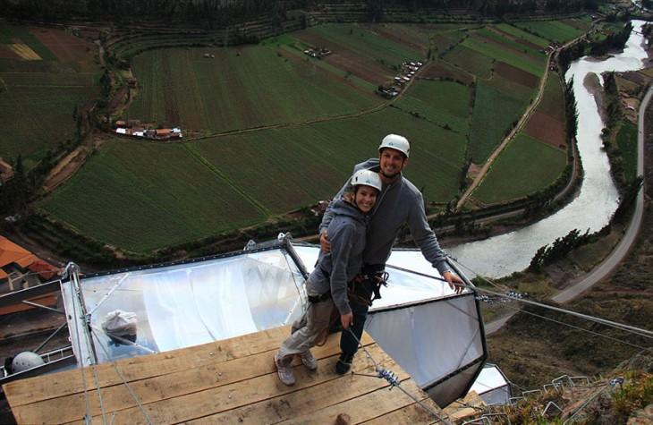 una pareja parada sobre una base madera al escalar una montaña